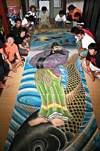 完成した鯉仙人の絵を中田さん(奥左)と眺める西2区の青年団員たち=いずれも七尾市石崎町で