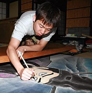 鯉仙人の目を描いて仕上げをする中田さん