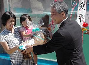 橋本館長から記念品を受け取る「鉄平」の名付け親の川越さん(左)=いずれも伊勢市の二見シーパラダイスで