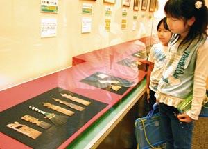 松山さんが再現に取り組んだ櫛に見入る児童たち=浜松市中区で