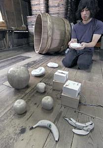 白いバナナなど陶芸作品の展示準備をする上出恵悟さん=金沢市東山1で