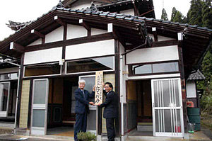 施設オープンで看板をかける中村理事長(左)と分家静男市長=射水市青井谷で