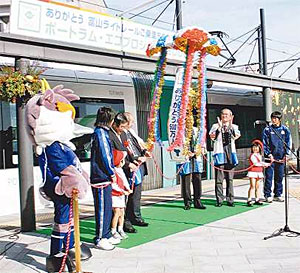 くす玉を割っ500万人達成を祝う関係者ら=富山ライトレール富山駅で