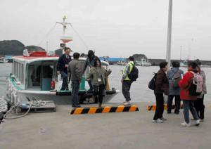 島での漁業体験イベント参加のため、遊覧船を下りる参加者ら=鳥羽市の桃取漁港で