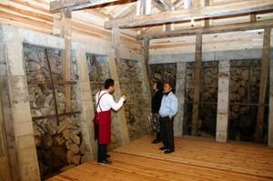 石積みから吹き出してくる冷たい空気を体感する人たち=松本市安曇の見学用風穴施設で