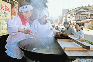 観光客らに振る舞われている道場六三郎さん考案の「新・カニ汁」=加賀市山中温泉で
