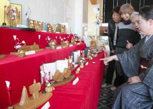 温かみあふれる木彫りのひな人形が並ぶ中村さんの作品展=鳥羽市の鳥羽国際ホテルで