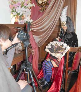 カーニバルの仮面をつけ記念撮影に臨む観光客=長浜市の黒壁ガラス館で