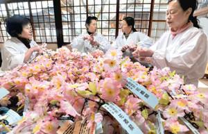 「花換まつり」を前に造花のサクラの小枝作りに励む女性たち=敦賀市の金崎宮で