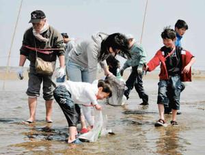 たて干し体験で魚を素手でつかんで楽しむ親子ら=津市藤方の御殿場海岸で