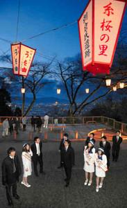 夜景をバックに、点灯したぼんぼりを眺める関係者=福井市の足羽山で