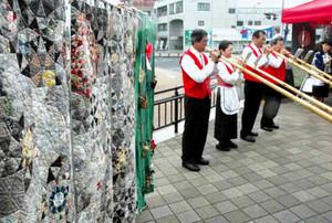 「のれんアート」の開幕を祝って演奏されるアルプホルン=恵那市大井町のJR恵那駅前で