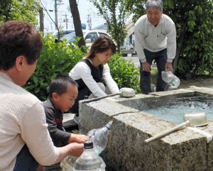 井戸からわき出る水をくむ家族連れ=安八町の井戸「しあわせの泉」で