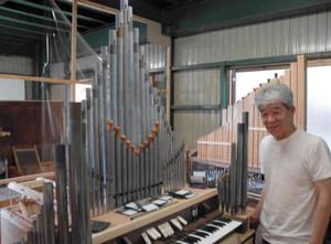 手作りで製作中のパイプオルガンと嶋村さん=大津市荒川で
