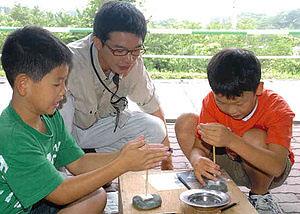 勾玉作りに挑戦する児童ら=魚津市歴史民俗博物館吉田記念郷土館で
