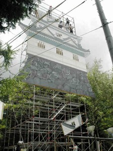 岩村城の「三重櫓」を再現したパネルを組み立てるメンバー=恵那市岩村町で