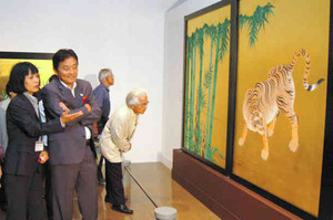 本丸御殿の玄関にあった「竹林豹虎図」の模写作品に目を凝らす河村市長(左から2人目)=名古屋市中区金山町の名古屋ボストン美術館で