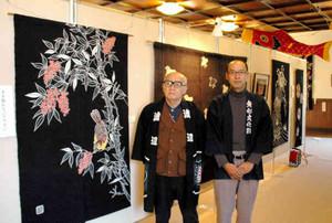 藍色が鮮やかな郡上本染展会場で作品紹介をする渡部庄吉さん(左)と一吉さん=郡上市八幡町で