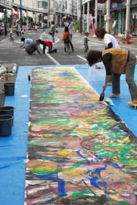 路上で絵を描く画家や道路に落書きする人たち=亀山市東町で