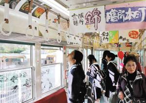 学生らの作品でにぎやかに飾り付けられた車内=大津市の京阪電鉄坂本駅で