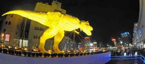 ライトアップされ、夜の市街地に姿を現した恐竜モニュメント=福井市のJR福井駅西口で