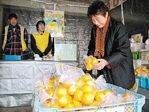 特売のユズを手に取る買い物客=砺波市庄川町金屋で