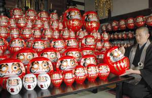 一つ一つ願いを込めて目を入れる小川寛行住職=稲沢市の尾張国分寺で