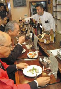 藤木シェフ(奥)の説明を聞きながら料理を楽しむ関係者=塩尻市で