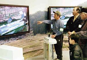 来園者(右)にトキの特徴などを紹介する協会関係者=いしかわ動物園で