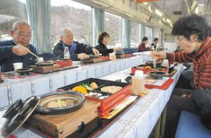 列車内で温かいイノシシ鍋と地元の山菜や川魚を味わう乗客=本巣市で