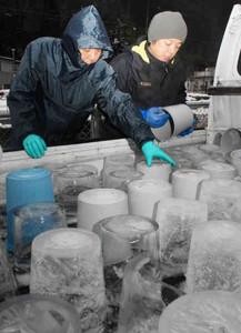 バケツからキャンドル用の氷を取り出す祭り実行委員ら=木曽町福島で