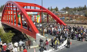 渡り初めを楽しむ人々でにぎわう天龍橋(奥は3代目の天龍橋)=飯田市龍江で