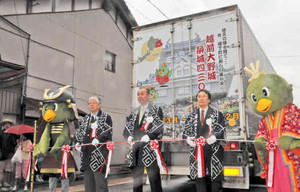 越前大野城築城430年祭をPRするラッピングトラックの出発を祝う岡田高大市長(中)ら=大野市の七間通りで