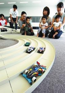室内サーキットでミニ四駆の試走に興ずる親子連れ=8日、島田市野田で