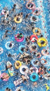 夏休み最初の日曜日、涼を求めて多くの人でにぎわうジャンボ海水プール=桑名市のナガシマスパーランドで、本社ヘリ「まなづる」から