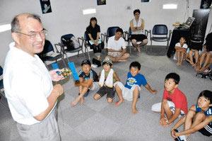 はやぶさの模型を使った解説に聞き入る児童たち=富山市天文台で