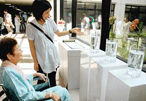 金沢美術工芸大の学生(右)と交流しながら作品を鑑賞する患者=金沢市平和町で