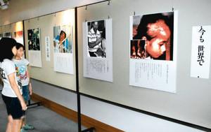 被爆者の写真や当時を伝える絵が並ぶ会場=金沢市立泉野図書館で