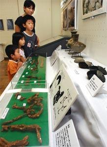 市内の遺跡からの出土品を見入る子どもら=静岡市葵区の静岡市民ギャラリーで