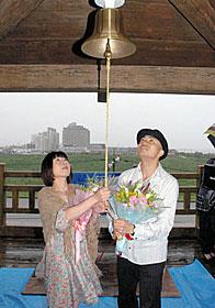 幸せへの鐘を鳴らす松田さん(右)と口出さん(右)