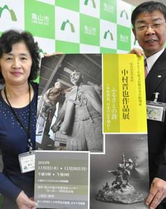 ポスターを手に個展への来場を呼び掛ける桜井義之市長(右)=亀山市役所で