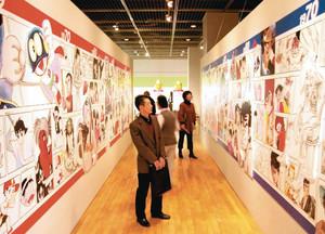 数々の人気漫画の年表を楽しむ人たち=四日市市立博物館で