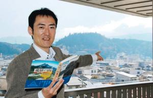 「飛騨の山」を手にする牛丸岳彦さん。中央にそびえるのは城山=高山市内で