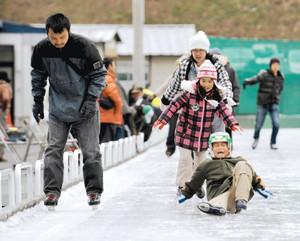 リンクで何度も転びながらもスケートを楽しむ家族連れ=松本市で