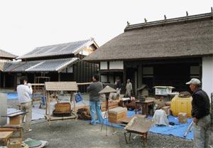 修理が完了した米蔵(左奥)と長屋門(右奥)の前で見学会の準備を進める関係者ら=菊川市下平川で