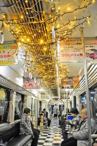 天井や床、座席などが飾り付けられたデコレーション電車を楽しむ乗客たち=福井市の福井鉄道田原町駅で