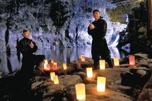 試験点灯で青白い光に浮かぶ霊蛇滝の前に並んだろうそくと忍者装束の関係者=名張市の赤目四十八滝で