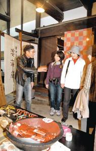 観光客に空き町家を利用した店の説明をする千賀伸一さん(左端)=近江八幡市で