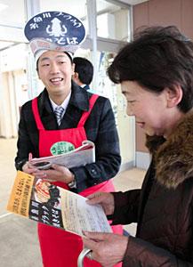 駅の利用客に向けて行われた「糸魚川ブラック焼きそば」のPR活動=JR富山駅で