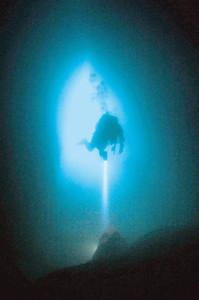 洞窟の入り口から差し込む光で幻想的な光に包まれる海中洞窟=尾鷲市の桃頭島で